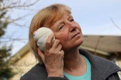 Reife Frau, die Muschel zum Ohr hält Lizenzfreie Stockfotos