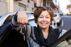 Reife Frau, die nahe Auto aufwirft Stockbilder