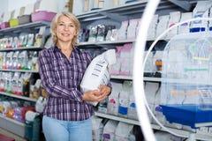 Reife Frau, die Nahrung für Haustiere im petshop kauft stockfotografie