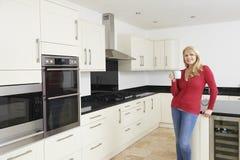 Reife Frau, die in neuer Luxus gepaßter Küche steht stockbild
