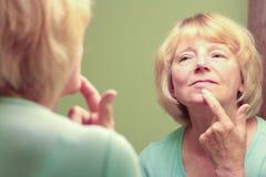 Reife Frau, die Reflexion im Spiegel betrachtet Stockbilder