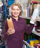 Reife Frau, die Shampoo im Speicher vorwählt stockbilder