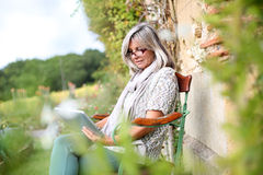 Reife Frau, die Tablette vom Garten verwendet Stockfotos