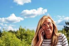 Reife Frau, die am Telefon plaudert Stockfotos