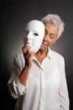 Reife Frau, die trauriges Gesicht hinter Maske revaling ist Stockfoto