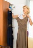 Reife Frau, die zu Hause Kleid wählt Stockbilder