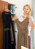 Reife Frau, die zu Hause Kleid wählt Stockfotografie