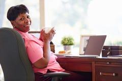 Reife Frau, die zu Hause Laptop auf Schreibtisch verwendet Lizenzfreie Stockfotos