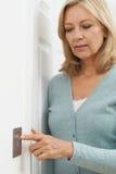 Reife Frau, die zu Hause Lichtschalter abstellt lizenzfreies stockbild