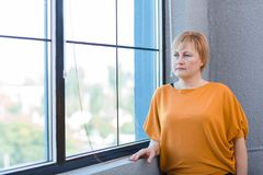 Reife Frau in einer gelben Bluse schaut heraus das Fenster stockfotografie