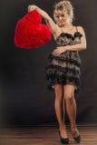Reife Frau hält großes rotes Herz Stockbilder