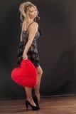 Reife Frau hält großes rotes Herz Stockfoto