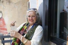 Reife Frau im Café mit kaltem Getränk Lizenzfreie Stockfotos