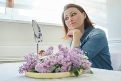 Reife Frau 40 Jahre alt, ihr Gesicht im Spiegel, weibliches Sitzen am Tisch zu Hause betrachtend, der Make-up tut stockfotografie