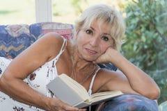Reife Frau liegt und Lesebuch auf einer Couch Stockfotografie