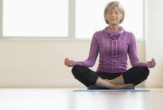 Reife Frau mit Augen geschlossenem Sitzen in Lotus Position Lizenzfreie Stockbilder