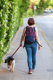 Reife Frau mit Bretagne-Hund auf einem Bürgersteig Stockfotografie