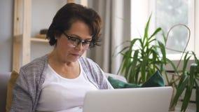 Reife Frau mit dem braunen Haar, in den Gläsern sitzt am Sofa stock footage