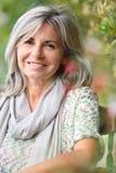 Reife Frau mit dem grauen Haarsitzen im Freien Lizenzfreie Stockbilder