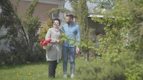 Reife Frau mit dem Korb mit den Tulpen in den Händen sprechend mit ihrem Enkel auf dem Hinterhof Erwachsener Enkel und stock video footage
