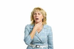 Reife Frau mit den schrecklichen Halsschmerzen stockbilder