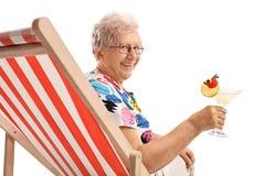 Reife Frau mit einem Cocktail, das in einem Klappstuhl sitzt Lizenzfreie Stockfotografie