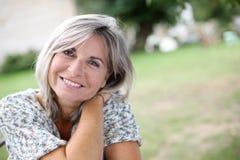 Reife Frau mit einem ruhigen Blick, der im Garten sitzt Lizenzfreie Stockfotografie