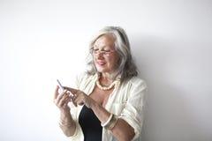 Reife Frau mit Gläsern unter Verwendung des Handys Stockbilder