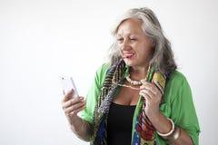 Reife Frau mit Gläsern unter Verwendung des Handys Lizenzfreie Stockbilder