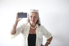 Reife Frau mit Gläsern unter Verwendung des Handys Stockfoto