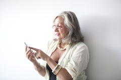 Reife Frau mit Gläsern unter Verwendung des Handys Lizenzfreies Stockfoto