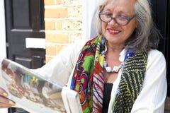 Reife Frau mit Gläsern Zeitung lesend Stockbild