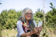 Reife Frau mit intelligentem Telefon Stockfotografie