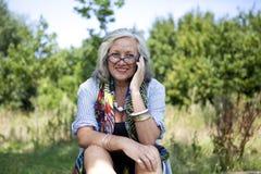 Reife Frau mit intelligentem Telefon Lizenzfreie Stockbilder