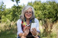 Reife Frau mit intelligentem Telefon Stockfotos