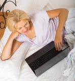 Reife Frau mit Laptop im Bett Stockbilder