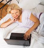 Reife Frau mit Laptop im Bett Stockfoto