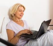 Reife Frau mit Laptop im Bett Stockbild