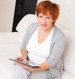 Reife Frau mit Tabletten-PC Lizenzfreies Stockbild