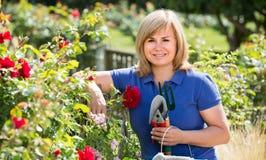 Reife Frau mit Werkzeugen im Garten Lizenzfreie Stockfotos