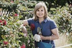 Reife Frau mit Werkzeugen im Garten Stockfotografie