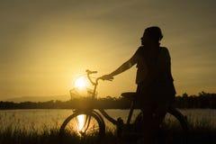 Reife Frau sitzen am Retro- Weinlesefahrrad nahe dem See am Sonnenuntergangmoment Schattenbildfahrrad bei dem Sonnenuntergang mit Stockbilder