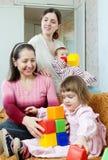Reife Frau und ihre erwachsenen Tochterspiele mit Kindern stockfoto