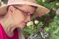 Reife Frau und Weißrose lizenzfreies stockbild