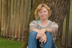 Reife Frau unter Baum Stockfotos