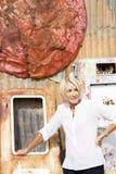 Reife Frau unter verrostendem Metall im Schrottplatz Stockbild