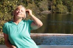 Reife Frau, welche die Sonne in der Natur genießt Lizenzfreies Stockbild