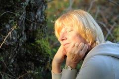Reife Frau, welche draußen die Sonne genießt Lizenzfreie Stockfotografie
