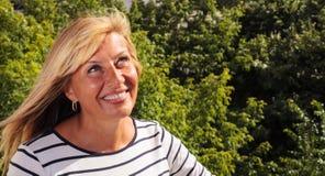 Reife Frauen-lächelndes oben schauen Lizenzfreie Stockfotografie