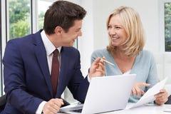 Reife Frauen-Sitzung mit Finanzberater zu Hause lizenzfreie stockfotografie